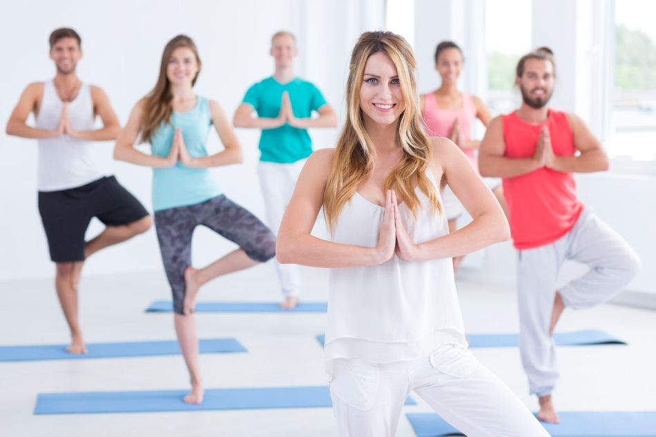 61536576 - shot of young woman instructing a group in pilates class