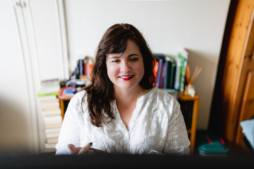 Image of me; I'm facing my computer screen and smiling; I'm sitting in front of a bookcase and wearing a white shirt.