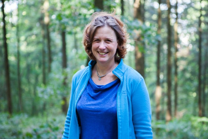 Jane Eggers smiling at the camera. She has chin-length, wavy brown hair and she's wearing a lovely dark blue top with a light blue jacket and a silver and blue necklace (silver chain and beads; blue flower pendant in the middle). She's standing in the woods with dappled sunshine.