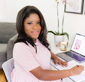 Monique Basil-Wright - Monique has black hair and dark skin that contrasts beautifully with her pale pink top and pink lipstick. She's sitting at a modern white desk with an open laptop and has turned to face and smile at the camera.