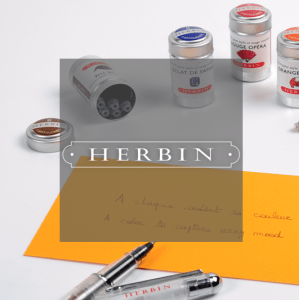 Herbin logo in front of ink cartridges and pen