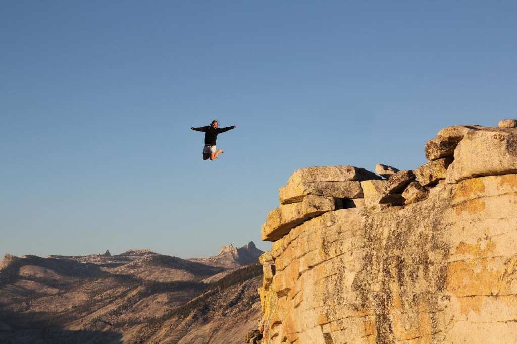 Training your inner caveman to take risks: man jumping off cliff