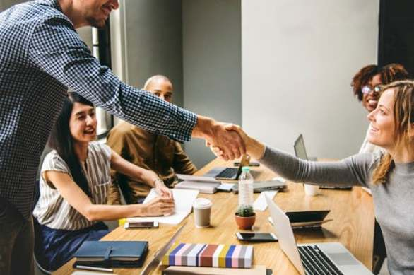 Colleagues-shaking-hands-at-desk-courtesy-unsplash-raw-pixel