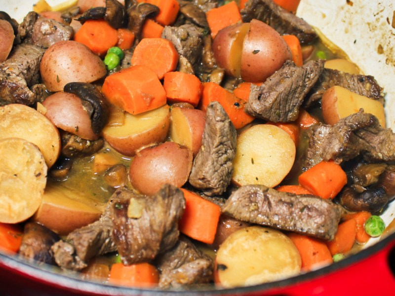 Stew in a pot with big bites of beef tenderloin, red potatoes, carrots, mushrooms, peas, and broth