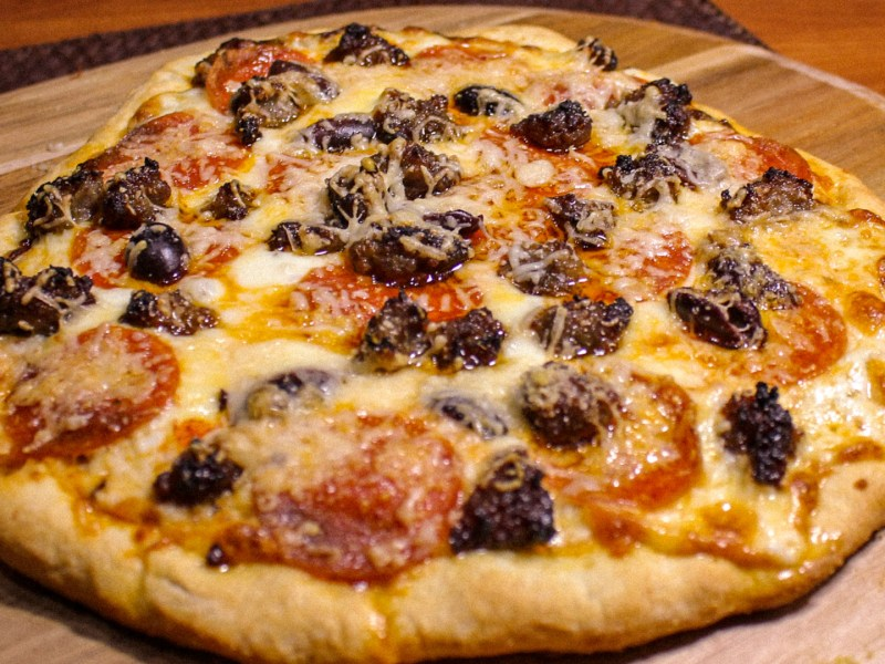 A whole pizza topped with pepperoni, sausage, olives and cheese
