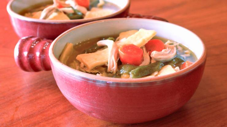 two bowls filled with chicken noodle soup. Carrots, chicken, green beans and thick dumpling-style noodles