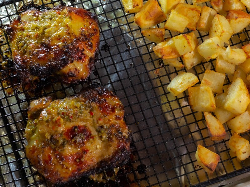 Two crispy chicken thighs on pan with roasted potatoes