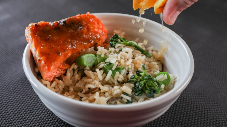 Orange juice squeezed on a bowl with rice and broccoli and a piece of salmon on the side