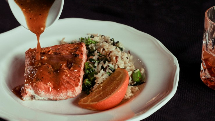 Sauce pouring onto a piece of salmon plated with rice pilaf