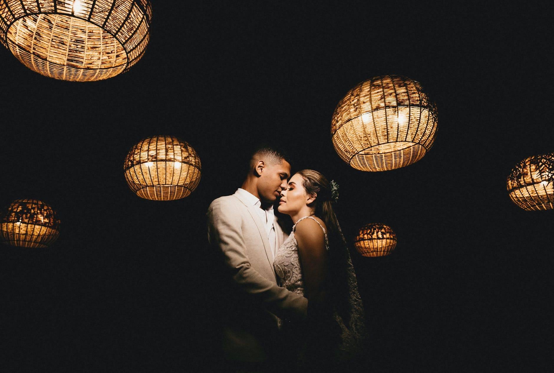 loving ethnic newlyweds hugging in dark studio