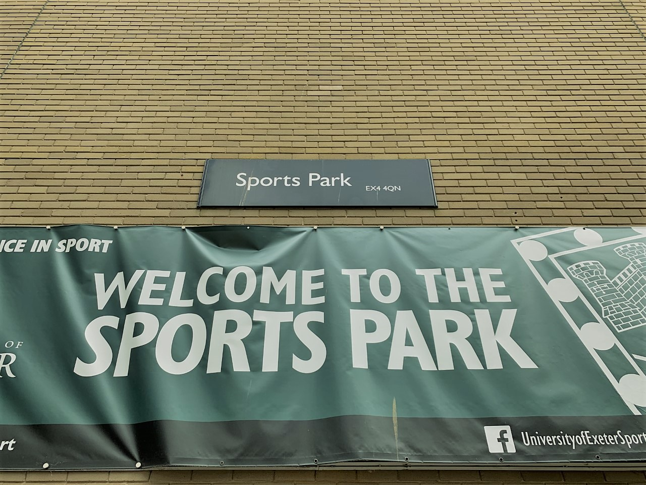 """""""Welcome to the Sports Park"""" banner on the wall of the Sports Park building on Streatham Campus"""