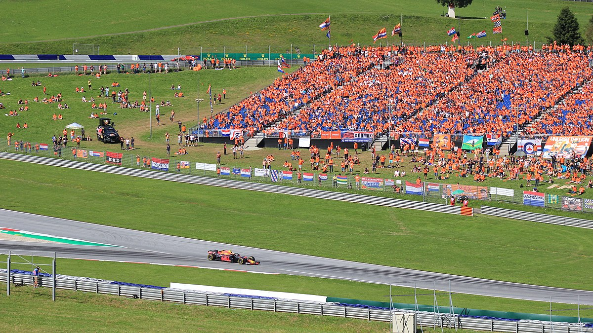 Race car on the tracks in front of a crowd wearing orange shirts