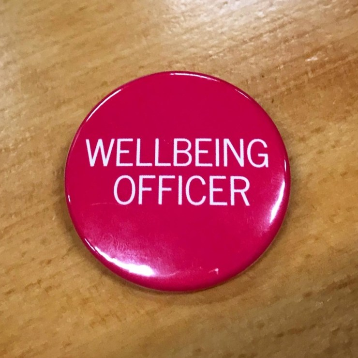 A circular pink badge that says wellbeing officer
