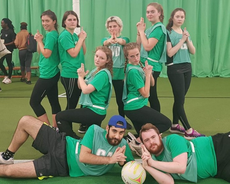 A team of people wearing green netball bibs