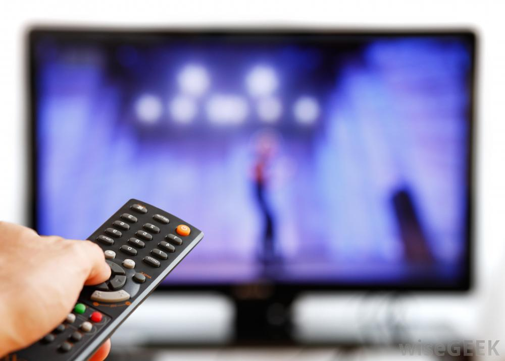 Hand Holding A Remote Pointed At A Flat Screen Television