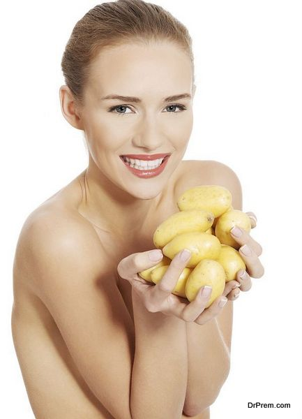 Beautiful naked woman holding raw potatoes in hands.