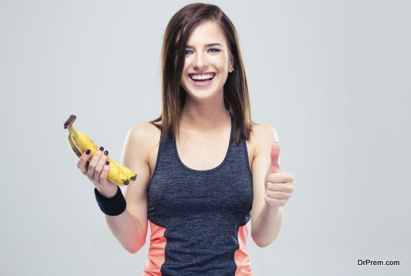 Woman holding banana and showing thumb up