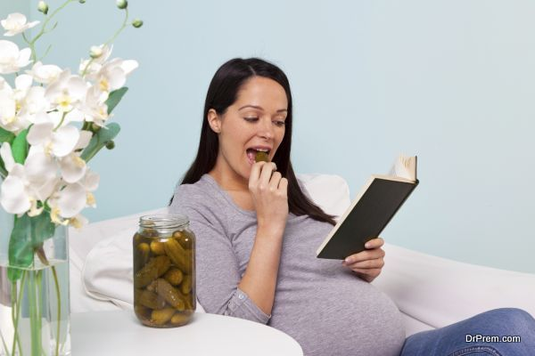 Pregnant woman eating a pickled gherkin.