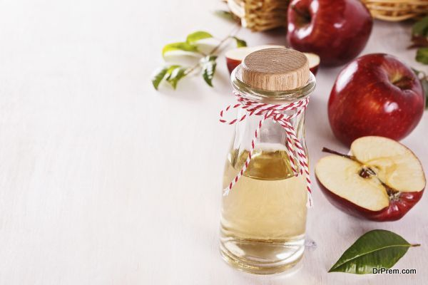 Apple cider vinegar over white wooden background