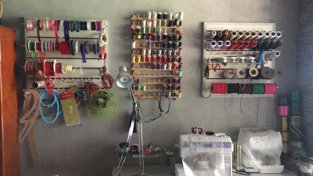 Pared con exhibidor de listones y exhibidor de conos de hilos y exhibidor de herramientas.