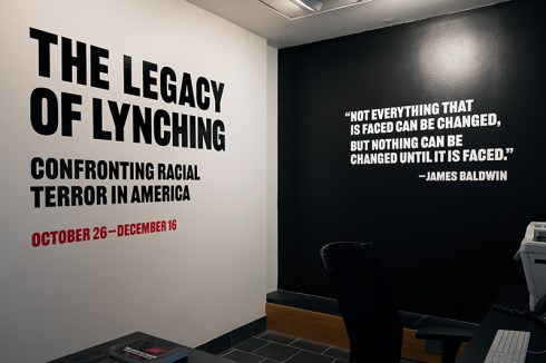 Vinyl wall displaying show title and a quote by James Baldwin