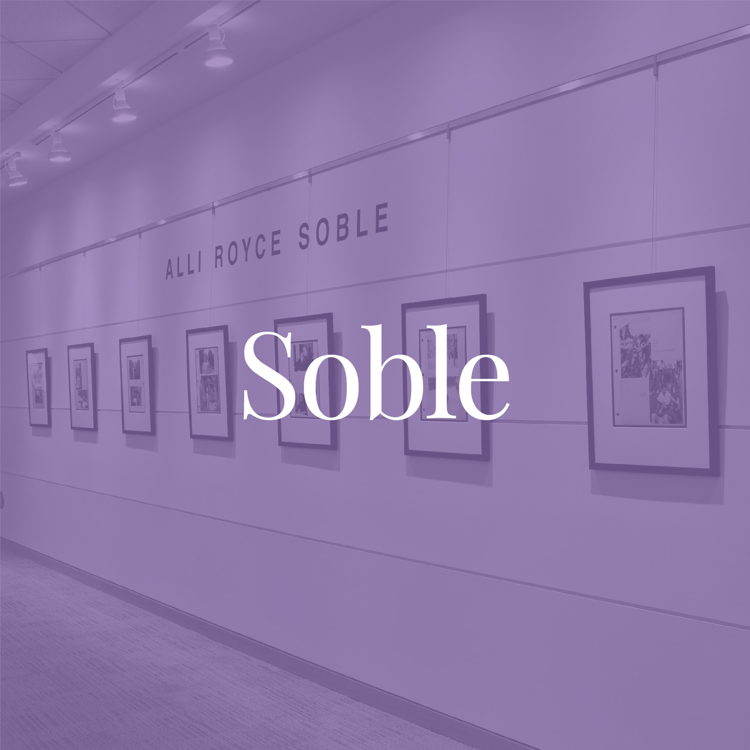 Purple-tinted photograph of Soble's scrapbook pages on display in the corridor of Emory University's Woodruff Library