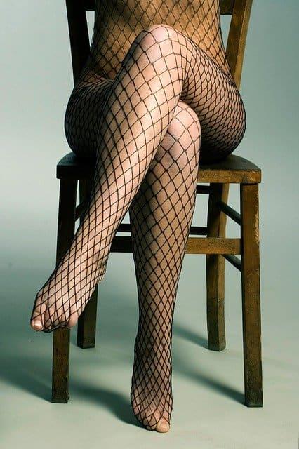 יושבת על כסא עם גרבי רשת