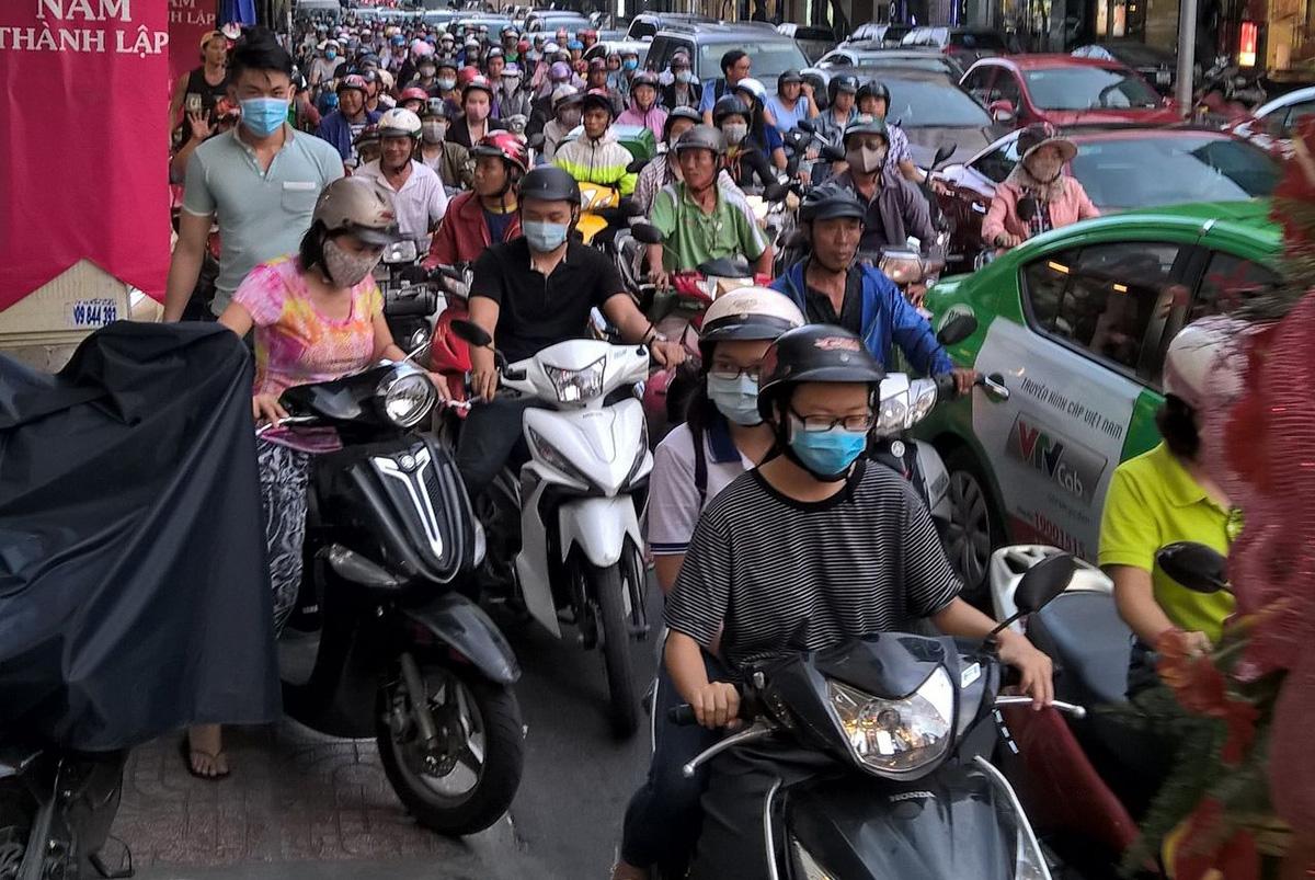 de máscara e moto, os vietnamitas vão a qualquer lugar