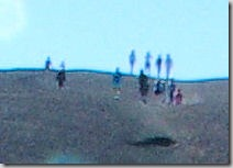 cropped closeup of people at the top of Inferno Cone, a cinder cone at Craters of the Moon National Monument, Idah