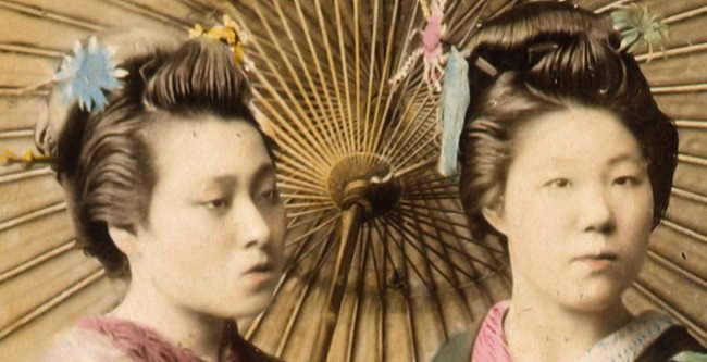 Two Japanese women, cropped from full-length studio portrait with backdrop, facing slightly right, standing with large parasol and holding hands