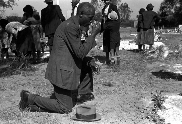 Man at grave of relative in cemetery, All Saints' Day, New Roads, Louisiana; photograph by Russell Lee