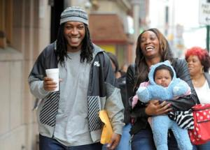 Sabein Burgess (L) walks with Latasha McFadden and their granddaughter, Gabrielle Davis, 5 months-old, after he was set free.