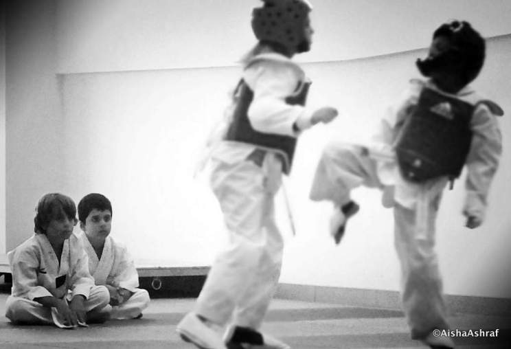 Two small Taekwondo students watch older students sparring