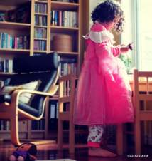 Small girl standing in front of a window in a princess dress