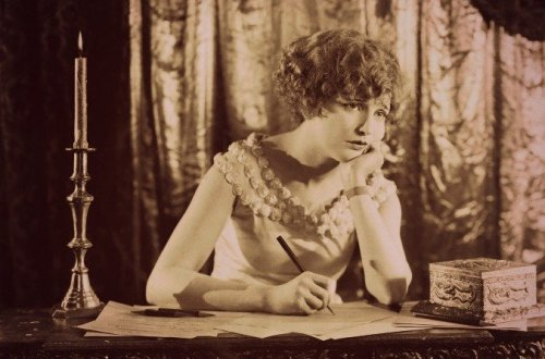 Female writer with her pen poised and her chin in her hand gazing into the distance