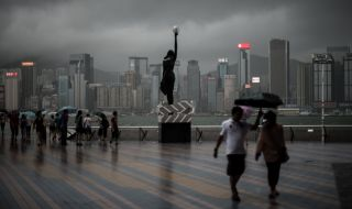 TOPSHOTS People walk under the rain in front of the Hong Kong skyline during a thunderstorm caused by Typhoon Rammasun on July 18, 2014. China on July 18 braced for a powerful super typhoon heading for its southern coast after the storm left a trail of destruction and at least 54 dead in the neighbouring Philippines.   AFP PHOTO / Philippe Lopez