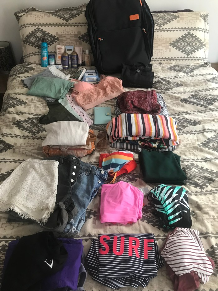 CLOTHES FOR 6 DAYS IN A TROPICAL LOCATION LAID OUT ON BED