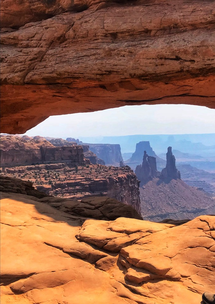 THE VIEW OF THE CANYON BELOW THROUGH MESA ARCH