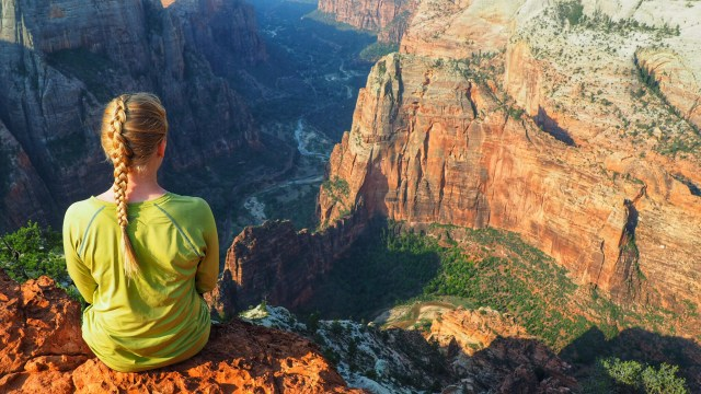 Girl sits on Canyon Edge at Observation Point in Zion National Park