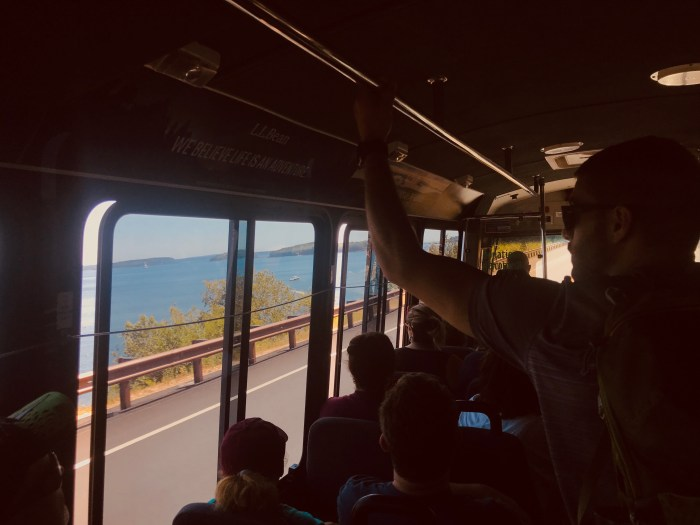 man holding railing looking out bus window at coast