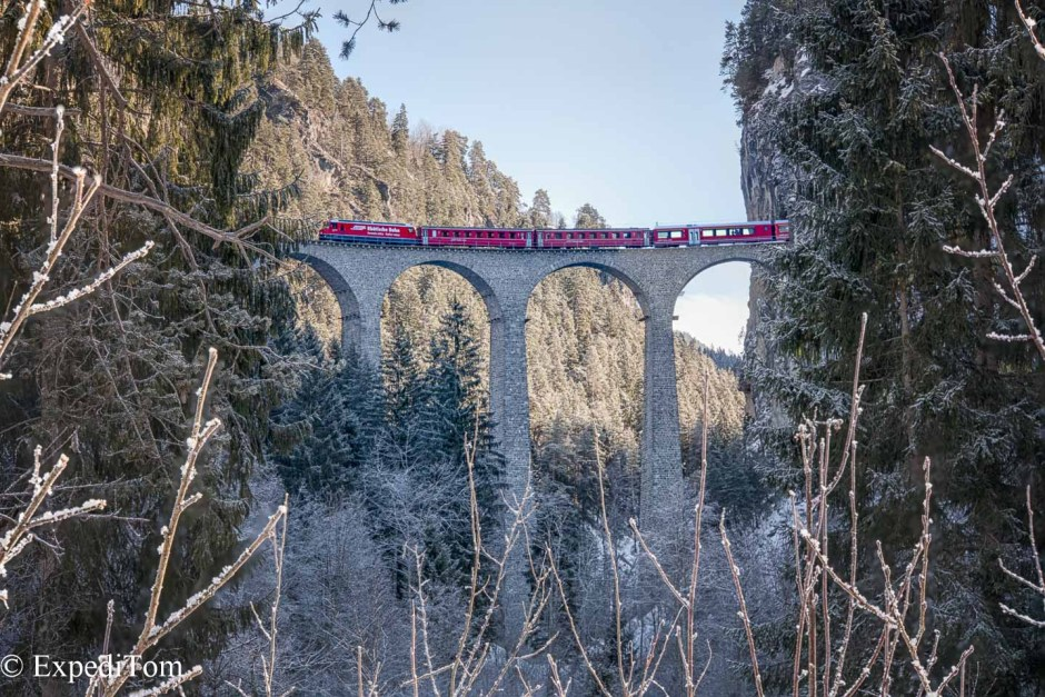 This view of the Landwasser Viaduct in Switzerland is more original by faming it with some scrub and trees from some distance.