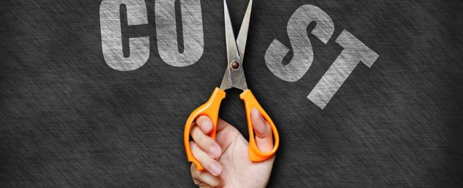 "Pictured: a pair of hands holding scissors are cutting through the word ""cost""."