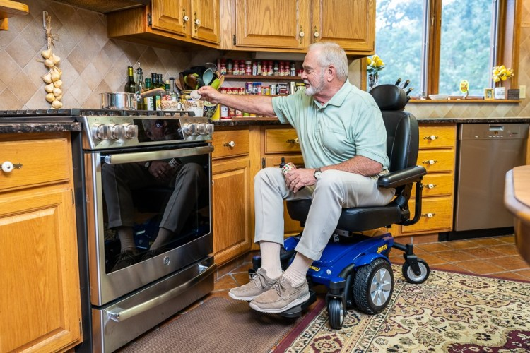 Man in a blue power wheelchair cooking a meal on the stove.