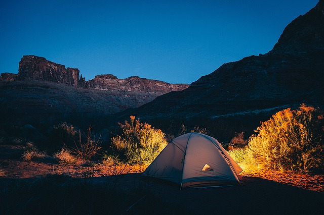 Evening scene of camping with a tent in front of a glowing fire