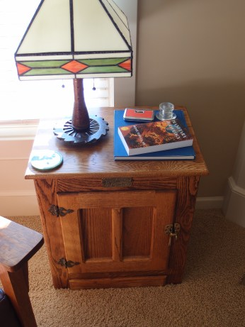 End table with lamp, opera glasses, glass insulator, and books