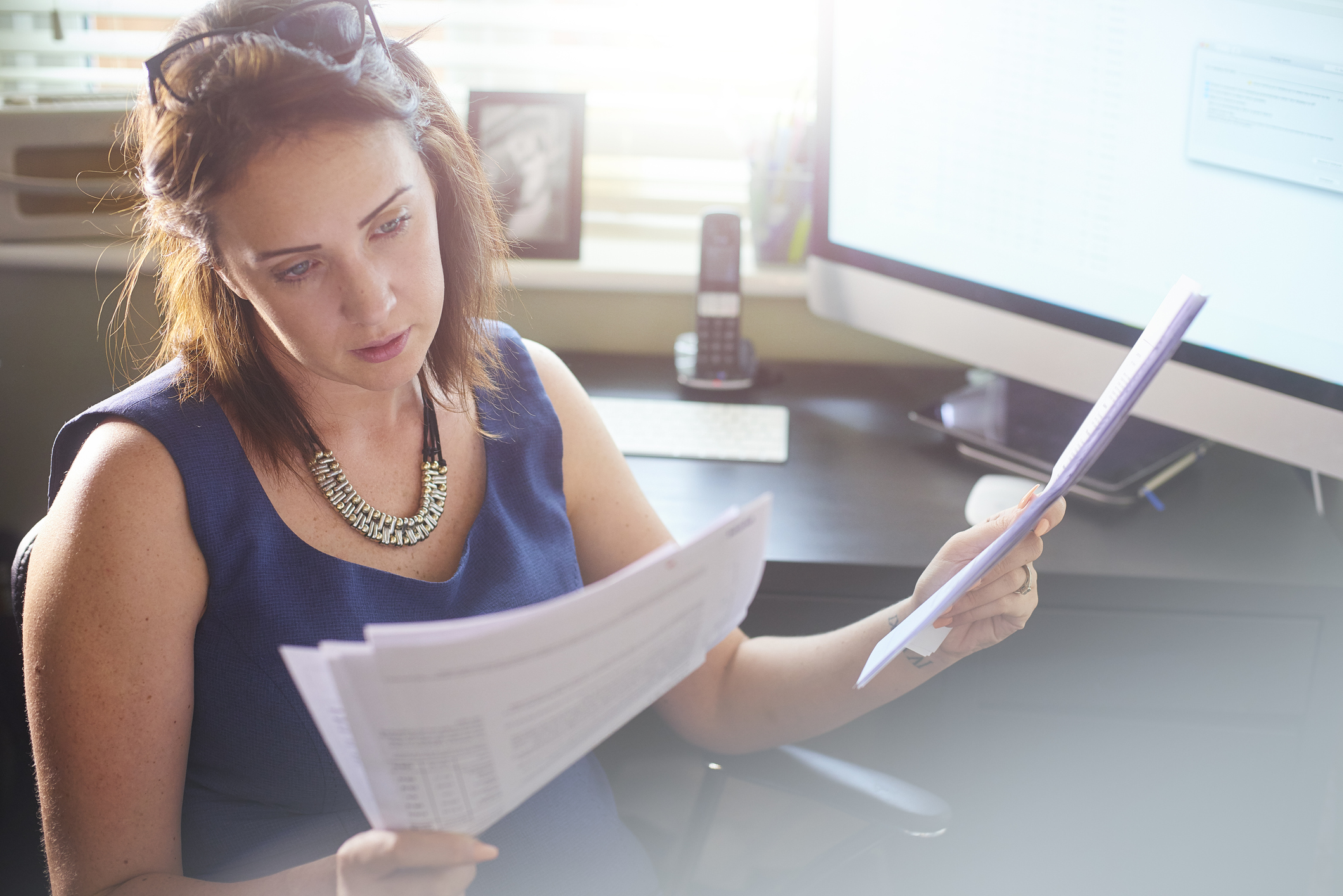 woman sits at her desk reading through paperwork