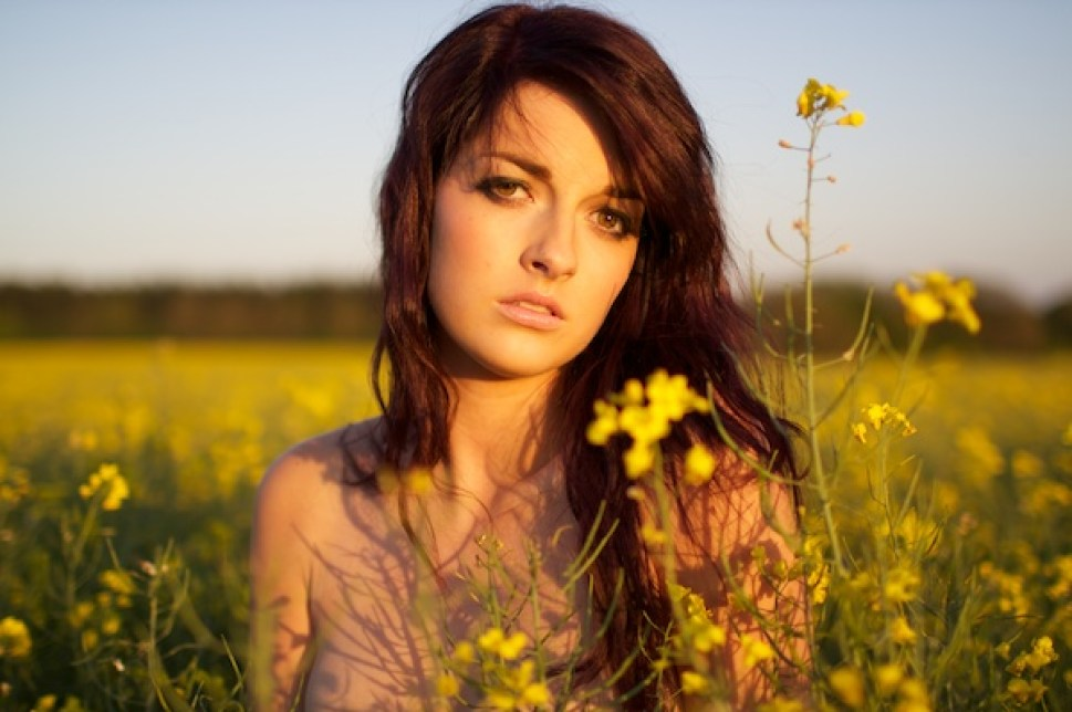 Photo of a young woman in the field of yellow flowers looking into the camera