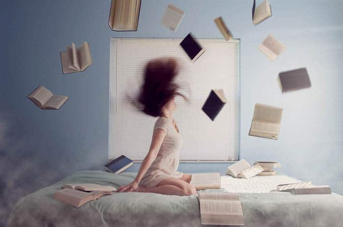 A conceptual portrait of a girl in her bedroom surrounded by flying books -