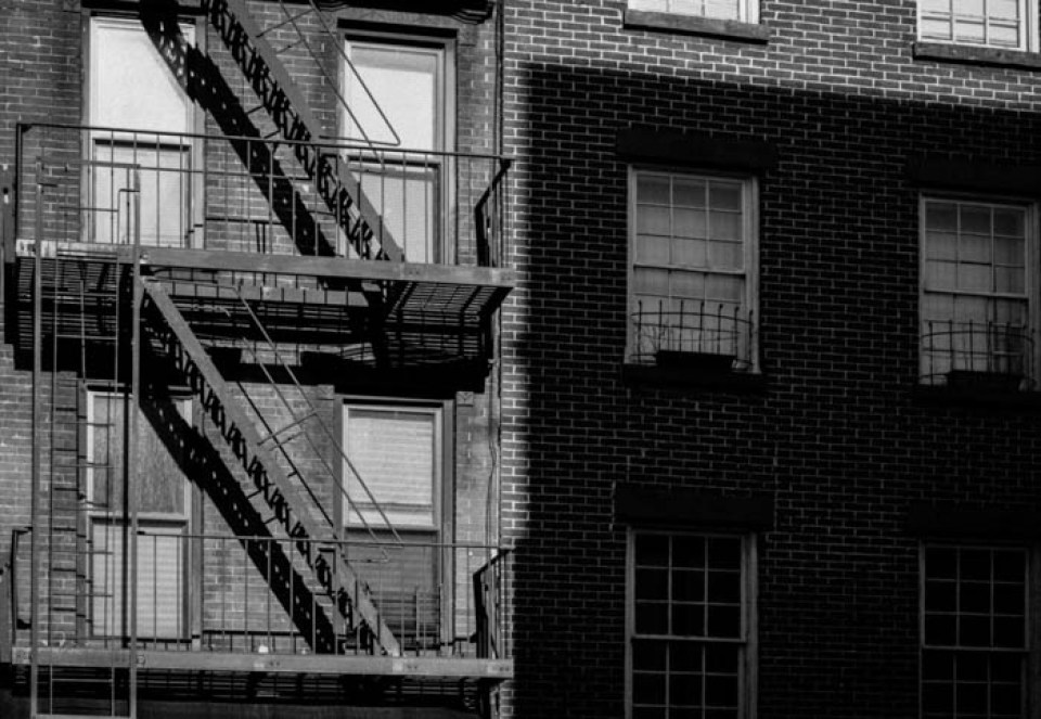 Greyscale photo of a stairway on the exterior of a building