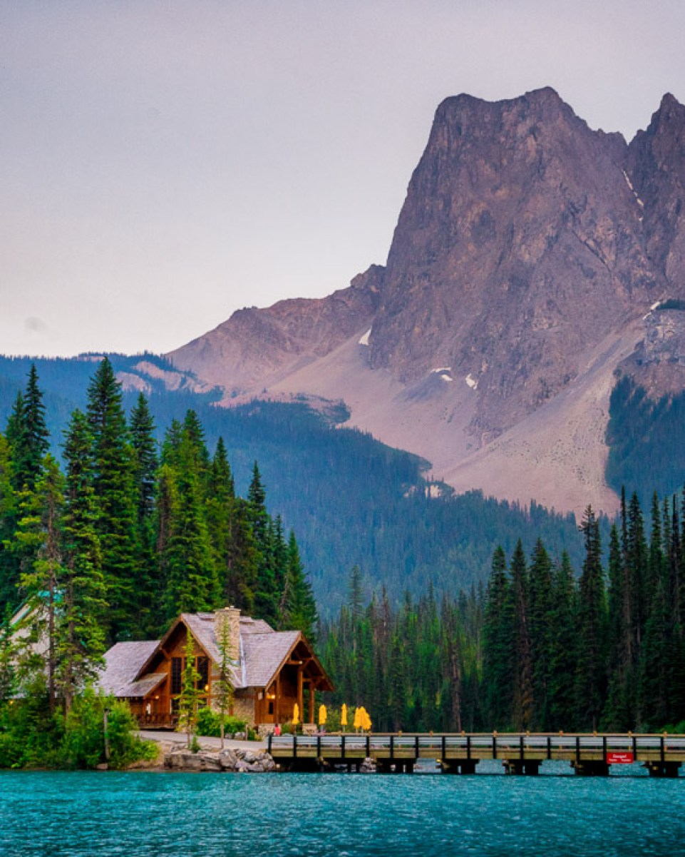 Stunning landscape photo composition of mountains above a small house, pier and lake